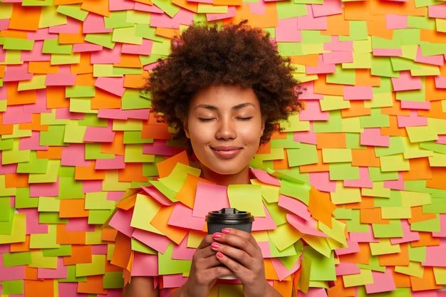 Ruhige, entspannte frau trinkt kaffee zum mitnehmen, hält die augen geschlossen, denkt über etwas angenehmes nach, trinkt gerne ein erfrischendes getränk, umgeben von bunten aufklebern. menschen, lifestyle-konzept
