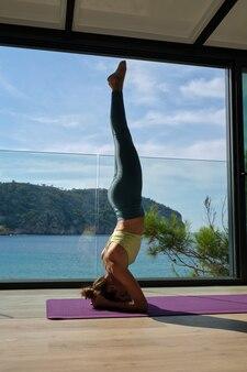 Ruhige frau, die yoga in unterstütztem kopfstand-asana praktiziert