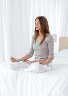 Ruhige frau, die yogaübungen auf dem bett tut