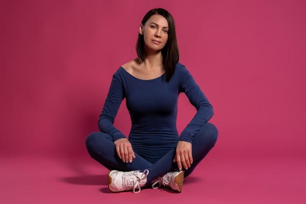 Ruhige frau im fitness-overall sitzt im schneidersitz auf dem boden