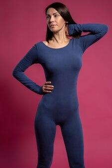 Ruhige frau im yoga-overall, die auf kastanienbrauner oberfläche steht