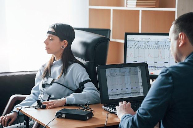 Ruhige frau. mädchen geht lügendetektor im büro vorbei. fragen stellen. polygraphentest