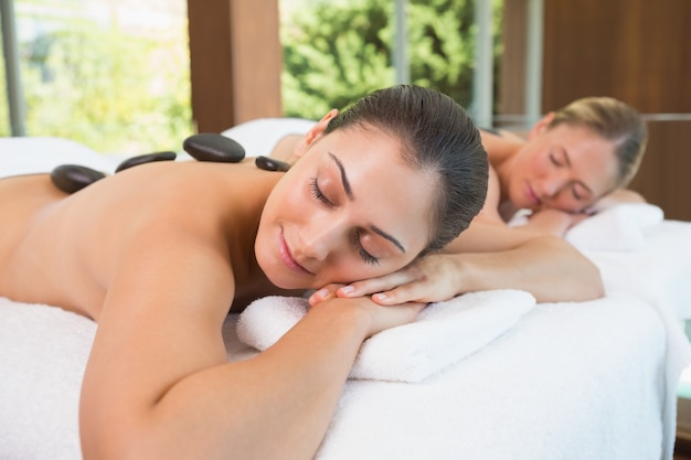 Ruhige freunde liegen auf massagetischen mit heißen steinen auf dem rücken