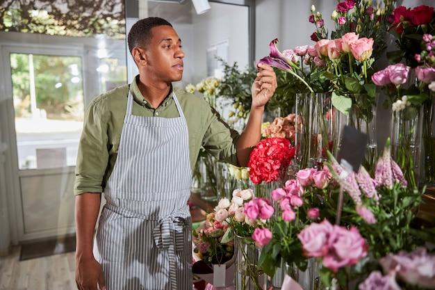 Ruhige, gemischtrassige person, die mit den fingern ein blütenblatt einer blume in einer vase hält