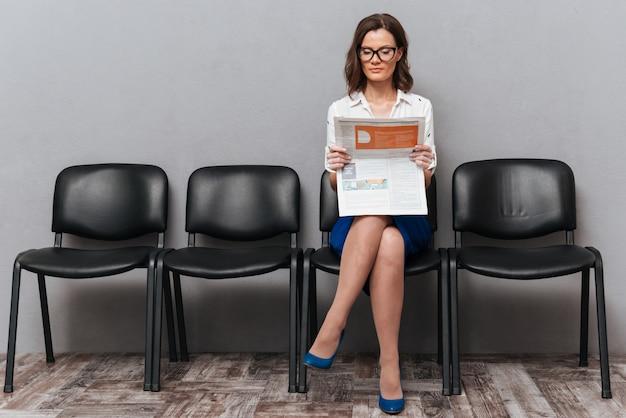 Ruhige geschäftsfrau in brillen, die auf stühlen sitzen