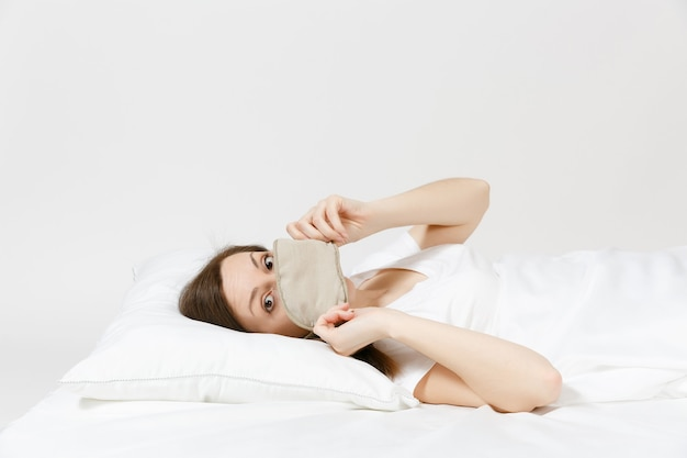 Ruhige junge brünette frau im bett liegend mit schlafmaske auf weißem laken, kissen, decke auf weißer wand