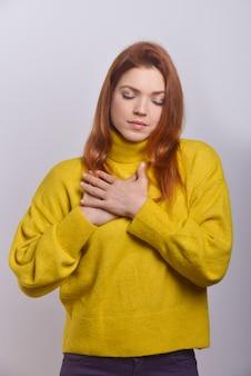 Ruhige junge frau mit den händen auf der brust