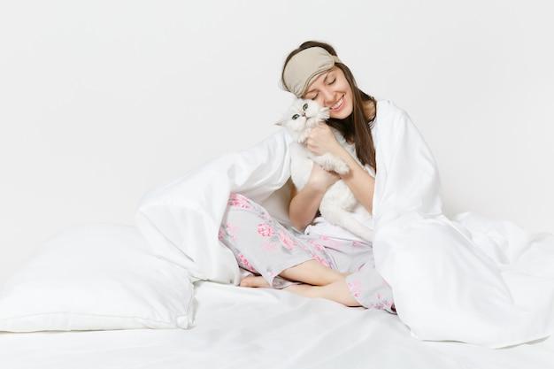 Ruhige junge frau sitzt im bett mit schlafmaske auf den augen isoliert auf weißer wand