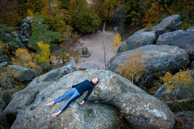 Ruhige junge frau übt yoga auf dem felsigen berg