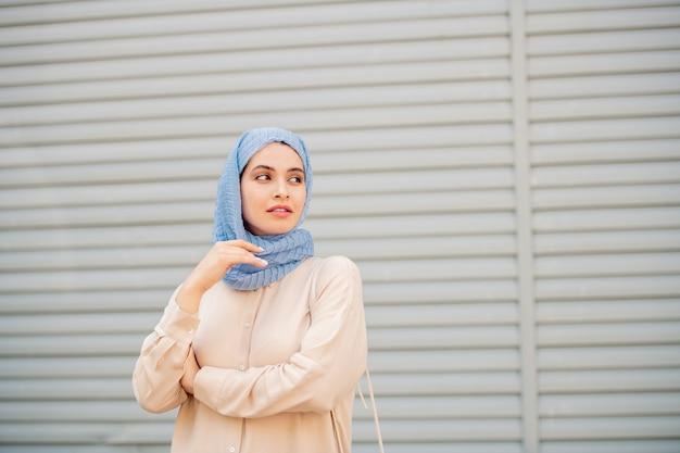 Ruhige junge muslimische frau im hijab, die auf taxi oder jemanden wartet, während sie draußen an der wand steht