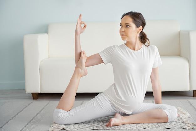 Ruhige junge schwangere brünette frau praktiziert ardha matsyendrasana yogaposition auf dem boden in der nähe des sofas in einem geräumigen zimmer zu hause