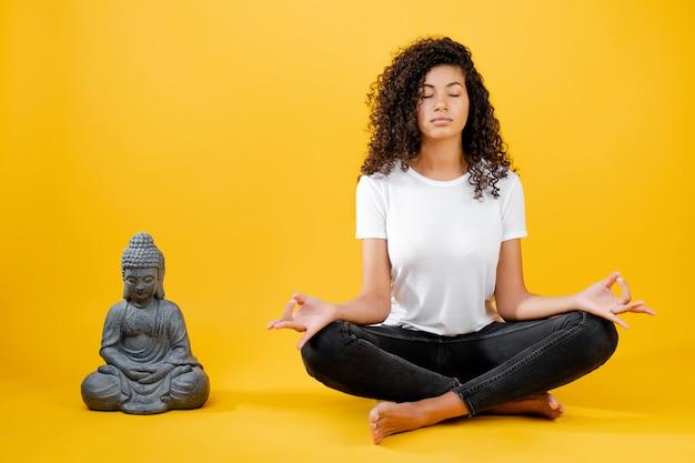 Ruhige junge schwarze frau, die yoga mit buddha lokalisiert über gelb meditiert und tut