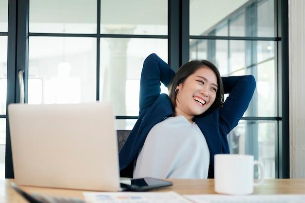 Ruhige lächelnde geschäftsfrau, die sich in bequemen bürostuhlhänden hinter dem kopf entspannt, glückliche frau, die sich nach getaner arbeit im büro ausruht Premium Fotos