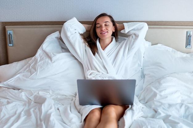 Ruhige lächelnde träumende freiberuflerin mit händen hinter dem kopf, die weiße bademantelfernbedienung trägt, die online an einem computer auf dem bett von einem hotelzimmer arbeitet. einfacher lebensstil und zufriedenheit