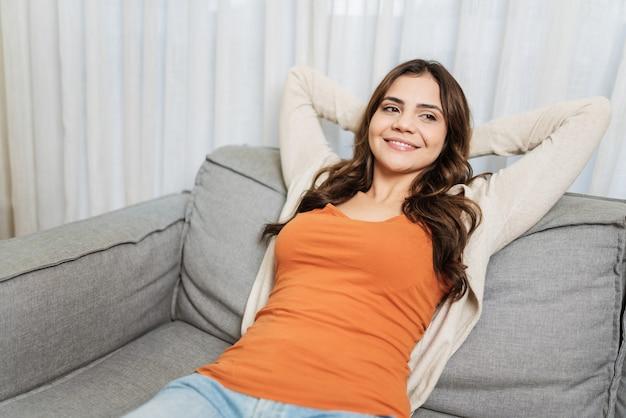 Ruhige lateinamerikanische frau, die sich auf einem weichen und bequemen sofa entspannt und stressfrei auf dem sofa genießt
