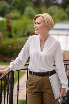 Ruhige, nachdenkliche, attraktive, exquisite blonde dame mit einem notebook-computer in der hand, die in die ferne blickt