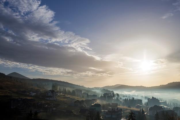 Ruhige nebelhafte landschaft, ländliches herbstpanorama unter hellem blauem himmel an der dämmerung oder an der dämmerung. schöne, im bau befindliche ferienhäuser in einem nebligen tal mit bewaldeten hügeln und bergen am horizont.