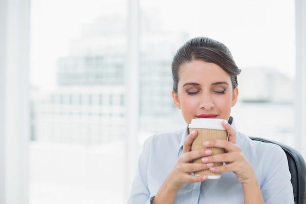 Ruhige noble braune behaarte geschäftsfrau, die kaffeegeruch genießt