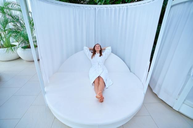 Ruhige, ruhige, brünette frau, die einen weißen bademantel mit geschlossenen augen und händen hinter dem kopf trägt, auf einer liege liegend und entspannende zeit genießt und sich in einem wellness-spa-resort wohl fühlt. einfacher lebensstil