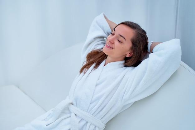 Ruhige ruhige frau im weißen bademantel mit geschlossenen augen und händen hinter dem kopf, die entspannende zeit genießt und sich in einem wellness-spa-resort wohl fühlt.
