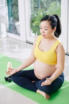 Ruhige schöne junge asiatische frau meditiert in lotussitz auf yogamatte, die einatmet und ausatmet