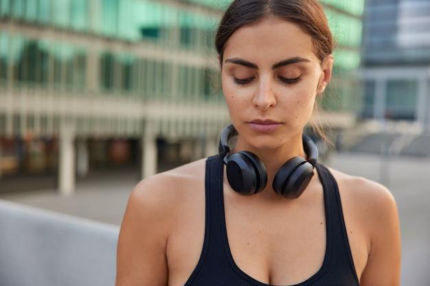 Ruhige sportlerin, die sich in activewear konzentriert, beendet trainingsposen gegen verschwommene