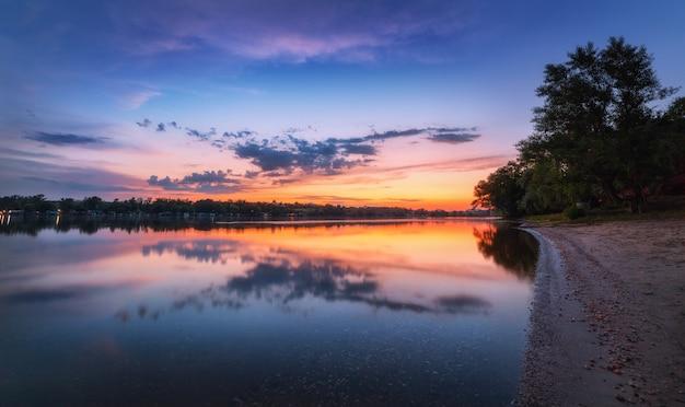 Ruhige szene mit fluss und buntem himmel mit wolken bei sonnenuntergang