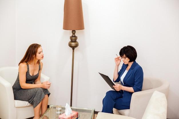 Ruhige und friedliche junge frau sitzt vor psychologen. sie hört ihr sehr genau zu. doktor betrachtet ihre tablette und hält eine hand nah an gläsern. sie denkt.