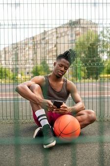 Ruhiger afrikanischer kerl in der sportbekleidung, die im smartphone während des sitzens auf dem basketballplatz durch zaun scrollt oder eine sms sendet