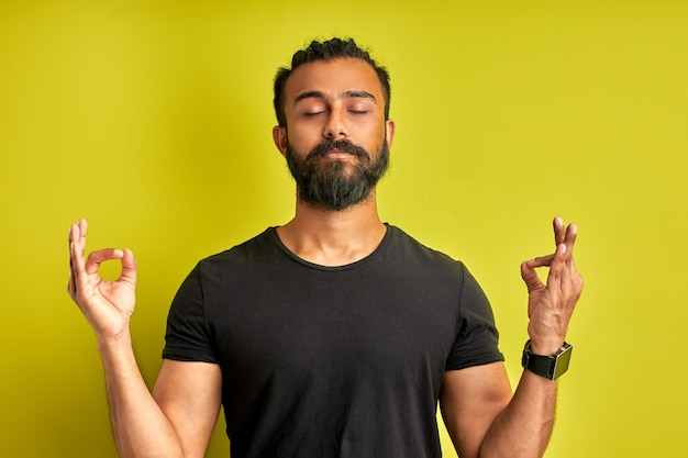 Ruhiger arabischer mann meditiert isoliert auf grünem hintergrund