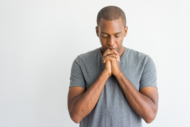 Ruhiger geistiger hübscher afrikanischer kerl, der mit geschlossenen augen betet.