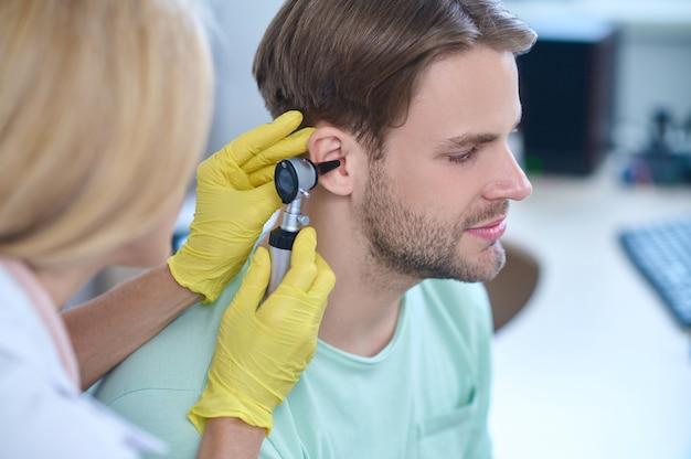 Ruhiger, gutaussehender, bärtiger, dunkelhaariger junger kaukasischer männlicher patient, der von einer professionellen hno-ärztin in sterilen handschuhen untersucht wird