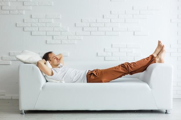 Ruhiger hübscher geschäftsmann, der zu hause auf couch nach der arbeit schläft