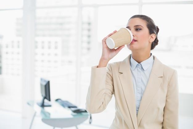 Ruhiger intelligenter trinkender kaffee der braunen behaarten geschäftsfrau