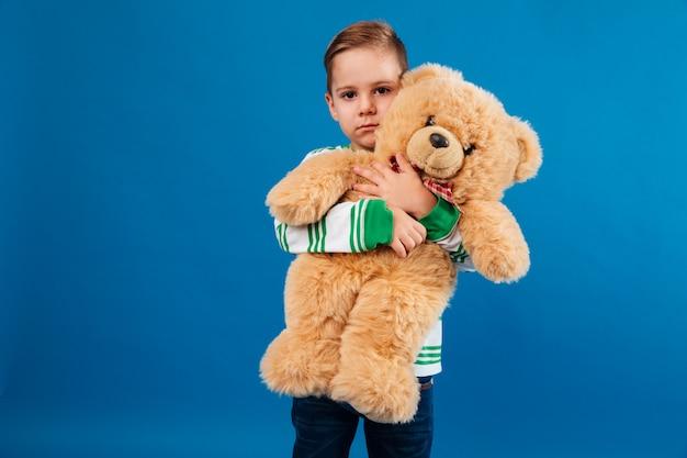 Ruhiger junge, der teddybär umarmt und schaut