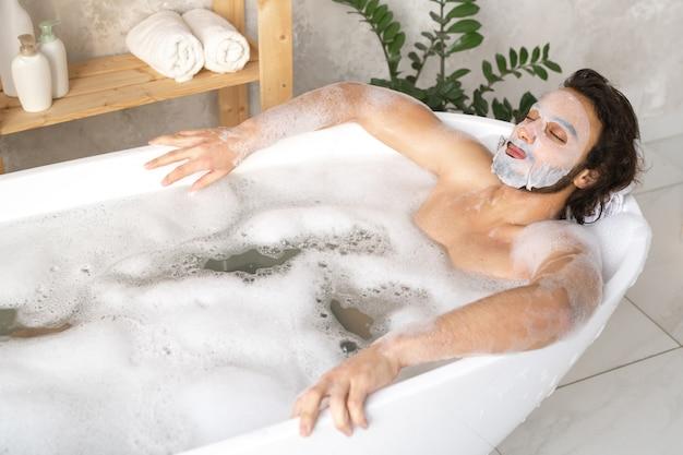 Ruhiger junger mann mit gesichtsmaske, die im heißen bad mit schaum entspannt, während er seine augen geschlossen hält