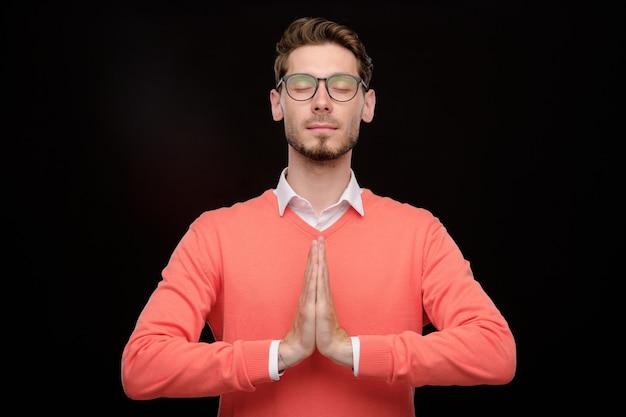 Ruhiger junger mann mit stoppeln, die hände in namaste halten, während mit geschlossenen augen gegen schwarzen hintergrund meditierend
