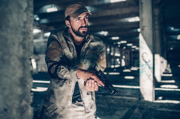 Ruhiger kämpfer trägt militäruniform. er steht neben der säule und achtet gut darauf. er schaut. guy hat eine schwarze pistole in den händen. auch der mensch hat einen finger am abzug.