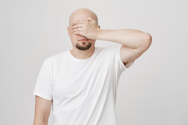 Ruhiger kahler bärtiger mann mittleren alters schloss die augen mit der handfläche