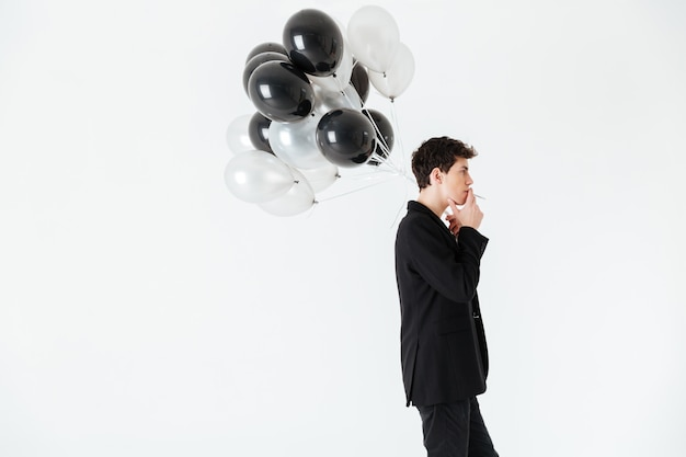 Ruhiger mann, der luftballons hält und zigarette raucht