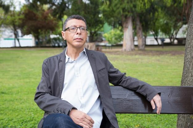 Ruhiger mann von mittlerem alter, der auf bank im park sitzt und sich entspannt