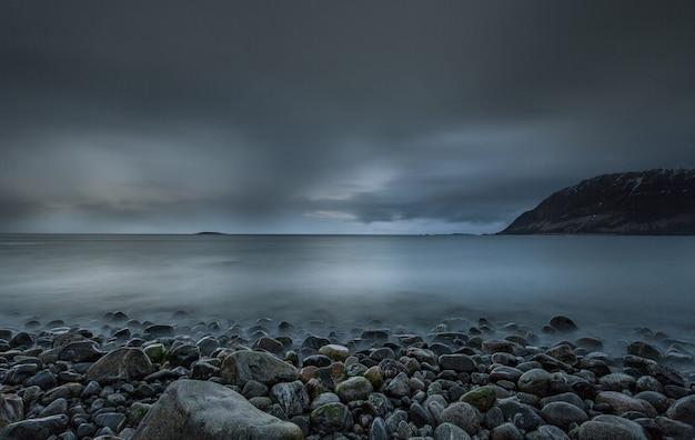 Ruhiger morgen am strand mit kalten farben des himmels, der im meer in den lofoten, norwegen reflektiert