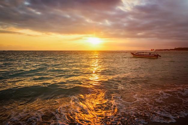 Ruhiger ozean mit boot auf sonnenaufgang