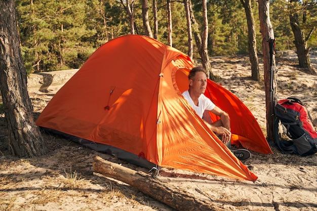 Ruhiger reifer mann geht nordic walking in der natur und entspannt sich nach aktivität im zelt