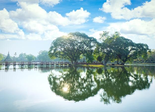Ruhiger see, umgeben von wald mit bunten bäumen, die sich im wasser spiegeln