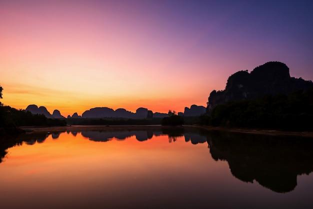 Ruhiger see und kalkstein-karst-gebirgsformation mit reflexion über wasser im morgengrauen mit dämmerungshimmel am frühen morgen, nong thale, krabi, thailand. berühmtes reiseziel in siam.