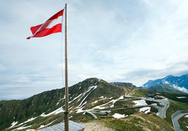 Ruhiger sommeralpenberg und österreichische flagge oberhalb der großglockner-hochalpenstraße