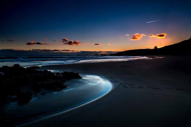 Ruhiger und entspannter malerischer strandplatz während des sonnenuntergangs in der dämmerung mit farbigem himmel