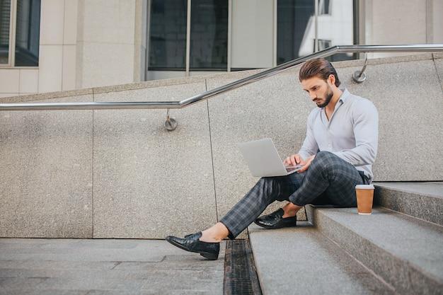 Ruhiger und friedlicher junger mann sitzt auf stufen und arbeitet. er schaut auf den laptop-bildschirm. es gibt plastikbecher kaffee auf stufen. er ist beschäftigt.