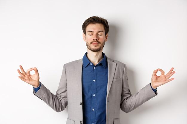 Ruhiger und konzentrierter geschäftsmann, der mit geschlossenen augen und seitlich gespreizten händen meditiert